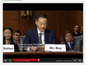 Kevin and Rich sit behind Norman Bay during Bay's Senate hearing, with Rich visible in this picture.