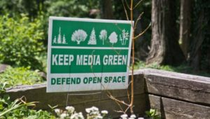 A sign protests a loss of open space in Media Borough