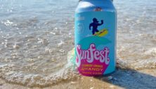A can of Sunfest Strawberry Lemonade Shandy placed on the sand by the ocean.